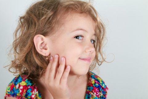 Девочка чувствует себя красавицей, любуясь подаренной сережкой.