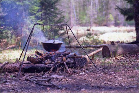 Костер туристов на привале с приспособлениями для приготовления пищи.