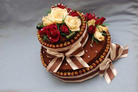 Торт с конфетами, украшенный розами.