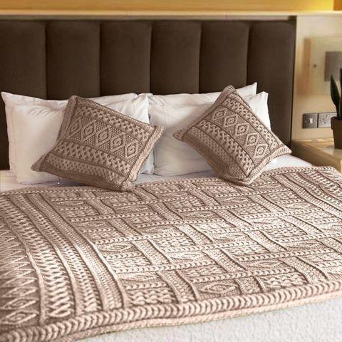Плед и подушки, связанные похожим узором.