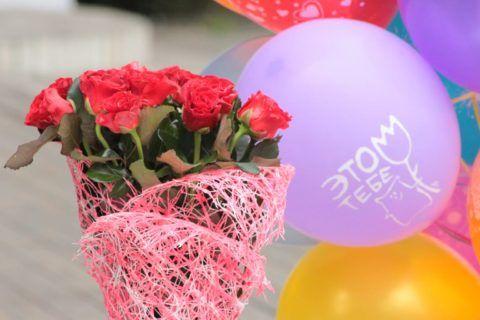 Девушка-старшеклассница обрадуется красивому букету цветов.